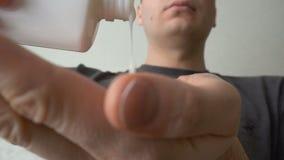 Το άτομο κινηματογραφήσεων σε πρώτο πλάνο χύνει στην παλάμη του μετα βάλσαμου ή λοσιόν ξυρίσματος χεριών στο λουτρό απόθεμα βίντεο