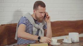 Το άτομο κουβεντιάζει από την τηλεφωνική συνεδρίαση στον καφέ και τον καφέ κατανάλωσης, χαμογελώντας ευτυχώς απόθεμα βίντεο