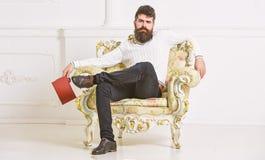 Το άτομο με τη γενειάδα και mustache κάθεται στην πολυθρόνα και την ανάγνωση, άσπρο υπόβαθρο τοίχων Ο ειδήμων, καθηγητής απολαμβά στοκ φωτογραφίες