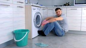 Το άτομο στα λαστιχένια γάντια έχει ένα υπόλοιπο από τον καθαρισμό και την ομιλία σε κάποιο που κάθεται στο πάτωμα κουζινών απόθεμα βίντεο