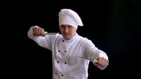 Το άτομο της καυκάσιας εμφάνισης στο λευκό σαν το χιόνι αρχιμάγειρα κοστουμιών σε ένα καπέλο αρχιμαγείρων που στέκεται σε μια θέσ απόθεμα βίντεο