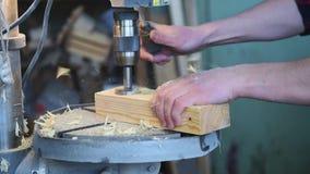 Το άτομο τρυπά τον ξύλινο φραγμό με τρυπάνι φιλμ μικρού μήκους