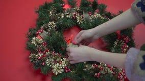 Το αγροτικό επίπεδο στεφανιών Χριστουγέννων βρέθηκε Χέρια που κρατούν τους κλάδους έλατου Παραγωγή του στεφανιού στο εργαστήριο φιλμ μικρού μήκους