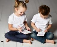 Το αγόρι και το κορίτσι δύο παιδιών στις άσπρα μπλούζες και το τζιν παντελόνι κάθονται το ένα κοντά στο άλλο και παίζουν το θωρηκ στοκ φωτογραφίες με δικαίωμα ελεύθερης χρήσης