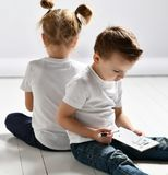 Το αγόρι και το κορίτσι δύο παιδιών στις άσπρα μπλούζες και το τζιν παντελόνι κάθονται το ένα κοντά στο άλλο και παίζουν το θωρηκ στοκ εικόνες