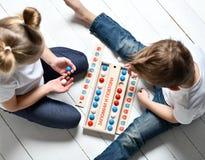 Το αγόρι και το κορίτσι δύο παιδιών στις άσπρα μπλούζες και το τζιν παντελόνι παίζουν το εκπαιδευτικό παιχνίδι θυμούνται και επαν στοκ φωτογραφία με δικαίωμα ελεύθερης χρήσης