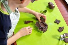 Το αγόρι συμπιέζει τις μορφές από τις φόρμες στην κυλημένη καφετιά ζύμη Οι πιεσμένες μορφές είναι δίπλα προετοιμασμένος για το ψή στοκ εικόνες με δικαίωμα ελεύθερης χρήσης