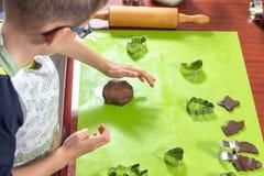 Το αγόρι συμπιέζει τις μορφές από τις φόρμες στην κυλημένη καφετιά ζύμη Οι πιεσμένες μορφές είναι δίπλα προετοιμασμένος για το ba στοκ φωτογραφία με δικαίωμα ελεύθερης χρήσης