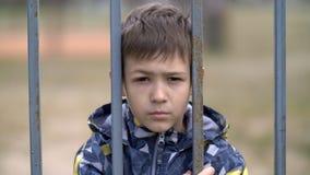 Το αγόρι πίσω από έναν φράκτη σιδήρου εξετάζει με την έχθρα τη κάμερα, κακό αγόρι με το μαυρισμένο μάτι στοκ φωτογραφίες