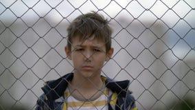 Το αγόρι πίσω από έναν φράκτη σιδήρου εξετάζει με την έχθρα τη κάμερα, κακό αγόρι στοκ φωτογραφία με δικαίωμα ελεύθερης χρήσης