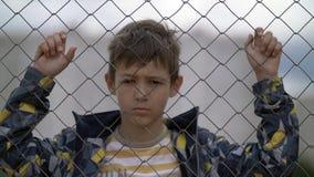 Το αγόρι πίσω από έναν φράκτη σιδήρου εξετάζει με την έχθρα τη κάμερα, κακό αγόρι στοκ φωτογραφίες με δικαίωμα ελεύθερης χρήσης