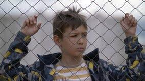 Το αγόρι πίσω από έναν φράκτη σιδήρου κοιτάζει με την έχθρα, κακό αγόρι στοκ φωτογραφία