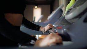το αθλητικό χαριτωμένο νέο κορίτσι brunette πηγαίνει μέσα για τον αθλητισμό treadmill απόθεμα βίντεο