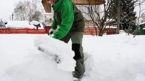 Το ανώτερο άτομο αφαιρεί το χιόνι στο ναυπηγείο φιλμ μικρού μήκους