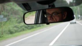 Το ανώτερο άτομο οδηγεί ένα αυτοκίνητο στη εθνική οδό Αντανάκλαση του προσώπου στον οπισθοσκόπο καθρέφτη του αυτοκινήτου closeup απόθεμα βίντεο