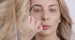 Το αρκετά ξανθό κορίτσι παίρνει ένα επαγγελματικό makeup από έναν θηλυκό καλλιτέχνη απόθεμα βίντεο