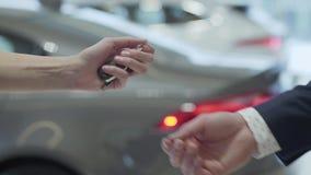 Το αρσενικό χέρι δίνει ένα αυτοκίνητο κλειδώνει στο famale παραδίδει στενό τον επάνω εμποριών αυτοκινήτων Παραγνωρισμένος αυτόματ απόθεμα βίντεο