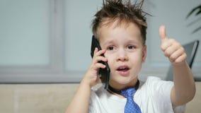 Το αστείο και ευτυχές αγόρι 3-4 χρονών επικοινωνεί σε ένα κινητό τηλέφωνο και παρουσιάζει έναν αντίχειρα Λίγος επιχειρηματίας απόθεμα βίντεο