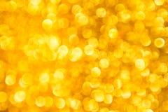 Το αφηρημένο χρυσό φως πολυτέλειας bokeh για το νέο υπόβαθρο έτους Χριστουγέννων στοκ εικόνες