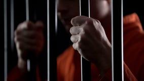 Το απελπισμένο εγκληματικό αίσθημα φραγμών φυλακών εκμετάλλευσης λυπάται για για την παράδοση της κινηματογράφησης σε πρώτο πλάνο στοκ εικόνες