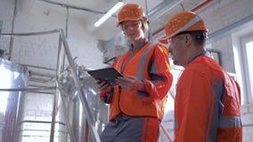 Το βαρύ εργοστάσιο βιομηχανίας, οι ευτυχείς αρσενικοί και θηλυκοί μηχανικοί στα σκληρά καπέλα συζητούν το νέο πρόγραμμα χρησιμοπο απόθεμα βίντεο