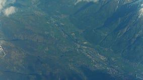 Το βουνό οξύνει, σύννεφα, απόμακρος αερολιμένας και αλπικές πόλεις σε μια κοιλάδα απόθεμα βίντεο