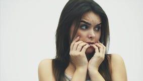 Το εκφοβισμένο τρελλό κορίτσι πήρε πολλή πίεση που τρίβει τα δάχτυλά της στο στόμα της η ανασκόπηση απομόνωσε το λευκό απόθεμα βίντεο
