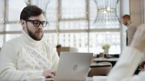 Το ενήλικο άτομο εργάζεται στη συνεδρίαση lap-top σε έναν καφέ με τη φίλη του ενώ μιλά πέρα από το smartphone απόθεμα βίντεο