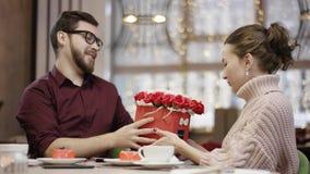 Το ενήλικο άτομο και η σύζυγός του κάθονται από τον πίνακα στο εστιατόριο και το άτομο καλεί το σερβιτόρο που φέρνει τα λουλούδια φιλμ μικρού μήκους