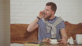 Το ενήλικο όμορφο άτομο μιλά από την κινητή τηλεφωνική συνεδρίαση στον καφέ το πρωί απόθεμα βίντεο