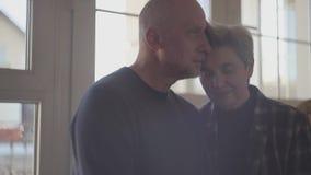 Το ενήλικο παντρεμένο ζευγάρι αγκαλιάζει ήπια τη συνεδρίαση σε ένα ευρύ παράθυρο Οικογενειακές σχέσεις φιλμ μικρού μήκους