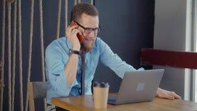 Το εύθυμο άτομο κοιτάζει στην οθόνη του σημειωματάριου και απαντά στην κινητή κλήση φιλμ μικρού μήκους