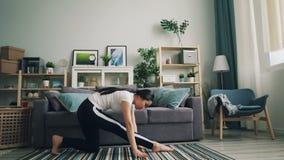 Το εύκαμπτο ασιατικό κορίτσι κάνει το τέντωμα ασκεί τη γιόγκα στο σπίτι άσκησης θέτει μόνο να βελτιώσει την υγεία της και τη φρον φιλμ μικρού μήκους