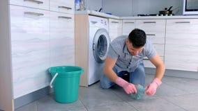 Το ευτυχές άτομο στα λαστιχένια γάντια πλένει και τριψίματα σκληρά το πάτωμα στην κουζίνα, καθμένος στο πάτωμα, πλάγια όψη απόθεμα βίντεο