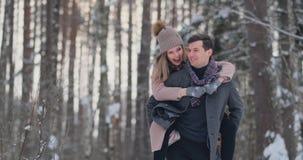 Το ευτυχές ζεύγος παίζει το χειμερινό αγώνα έξω από την απόλαυση του φωτός του ήλιου και του θερμού χειμερινού καιρού στα βουνά Τ φιλμ μικρού μήκους