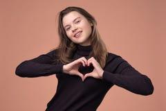 Το ευτυχές κορίτσι παρουσιάζει χειρονομία καρδιών εξετάζοντας τη κάμερα, χαμόγελο στοκ εικόνες με δικαίωμα ελεύθερης χρήσης