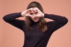 Το ευτυχές κορίτσι παρουσιάζει χειρονομία καρδιών εξετάζοντας τη κάμερα, χαμόγελο στοκ φωτογραφίες με δικαίωμα ελεύθερης χρήσης