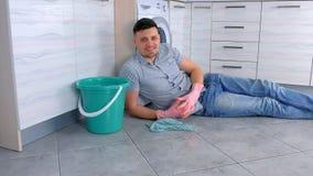 Το ευτυχές χαμογελώντας άτομο στα λαστιχένια γάντια έχει ένα υπόλοιπο από την τοποθέτηση καθαρισμού στο πάτωμα κουζινών απόθεμα βίντεο
