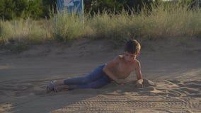 Το ευτυχές παιδί βρίσκεται στη σκόνη στεπών και η άμμος, απολαμβάνει το ελεύθερο παιχνίδι φιλμ μικρού μήκους