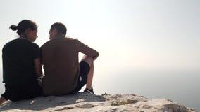 Το ζεύγος κάθεται στην άκρη ενός βουνού απόθεμα βίντεο