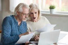 Το ηλικίας παντρεμένο ζευγάρι έλαβε τους απλήρωτους λογαριασμούς και οι φόροι αισθάνονται τονισμένοι στοκ εικόνα
