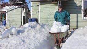 Το ηλικιωμένο άτομο καθαρίζει ένα εξοχικό σπίτι από το χιόνι απόθεμα βίντεο