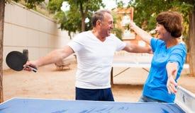 Το ηλικιωμένο ζεύγος απολαμβάνει τη νίκη στην επιτραπέζια αντισφαίριση σε υπαίθριο στοκ εικόνα