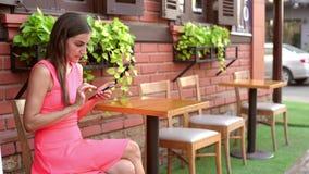 Το θηλυκό που μιλά στο τηλέφωνο, στέλνει τα μηνύματα σε έναν καφέ στην οδό 4K απόθεμα βίντεο