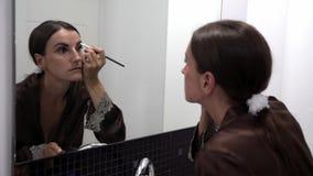 Το θηλυκό Brunette χρωματίζει τα φρύδια της με μια βούρτσα απόθεμα βίντεο