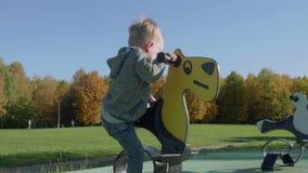 Το καυκάσιο ξανθό μικρό παιδί κατεβαίνει το ξύλινο άλογο στην παιδική χαρά φιλμ μικρού μήκους