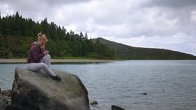 Το κορίτσι έχει τη διασκέδαση εξετάζοντας το smartphone στο υπόβαθρο της λίμνης και των λιμνών απόθεμα βίντεο
