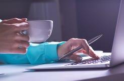 Το κορίτσι εργάζεται αργά στο σκοτεινό γραφείο με το lap-top Νέο κορίτσι επιχειρηματιών στην αρχή Φωτογραφία κινηματογραφήσεων σε στοκ εικόνα