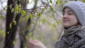 Το κορίτσι θαυμάζει και αγγίζει τα ανθίζοντας φύλλα με τα δάχτυλά της Υγρό χιόνι απόθεμα βίντεο