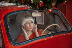 Το κορίτσι κοιτάζει στον καθρέφτη στο αυτοκίνητο στοκ φωτογραφία